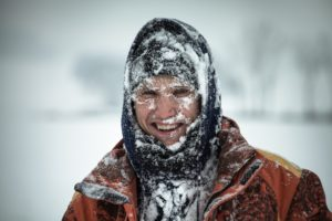 A young man is bundled up and covered in snow outside.