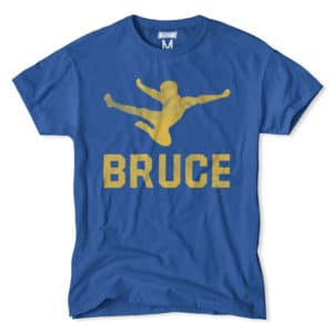 An outline of Bruce Lee's flying side kick flies off this blue graphic tee.