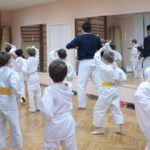 An room of eager, young martial artists follow the lead of their instructor.