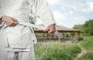A new martial arts student ties his white belt in preparation for class.