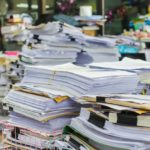 Stacks of papers and files bury the desks beneath them.