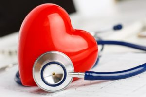 A stethoscope surrounds a heart resting on top of medical notes.