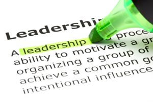 Green highlighter marks the importance of leadership on a textbook page.