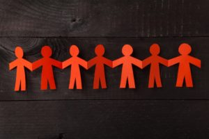 A chain of red paper men holds hands across a wooden table.