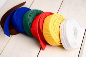 Several martial arts belts of all different colors are stacked in order on a wooden table.