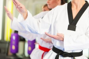 A black and red belt practice a form during martial arts class.