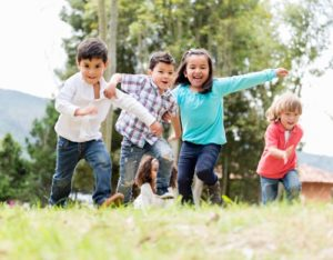 A group of young kids runs excitedly up a grassy hill.
