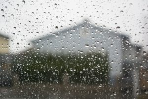 A window pane covered in rain drops blurs the image of a house on the other side.