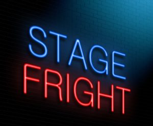 """A neon sign reading """"Stage Fright"""" beams brightly on a brick wall."""
