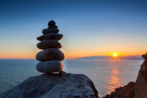 A stack of smooth rocks balances on a boulder overlooking a sunset over a peaceful ocean.