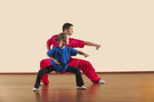 An experienced instructor demonstrates a martial arts stance to a young student.