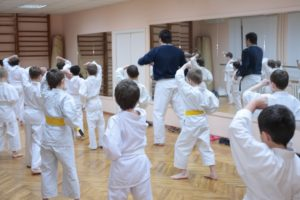 A room full of young martial artists follow their instructor's lead.