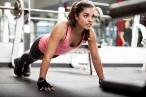 A woman looks ahead as she concentrates on the form of her pushups.
