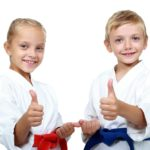Two young martial artists show they are having fun with a big thumbs up for martial arts.