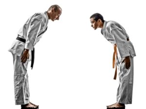 Martial arts instructor and student bow toward each other to demonstrate respect.