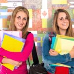 Two students cary notebooks on their way to class.