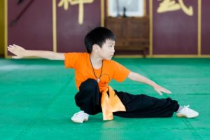 Young boy training in martial arts inside of a martial arts arts school