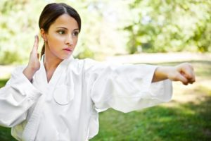Woman practices martial arts outside.